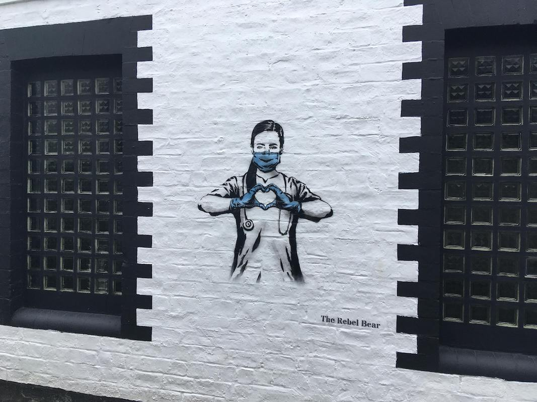 Wall art showing an NHS worker with a face mask making a heart with her hands