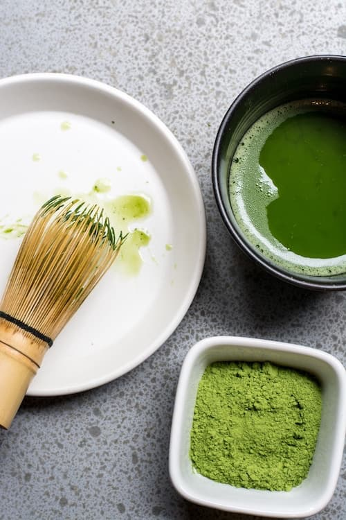 brush with green sauce and bowl of powdered wasabi