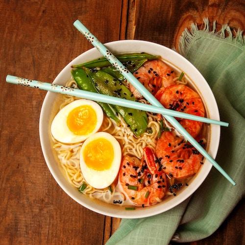prawn ramen bowl with egg, pees, sesame seeds, and blue chopsticks