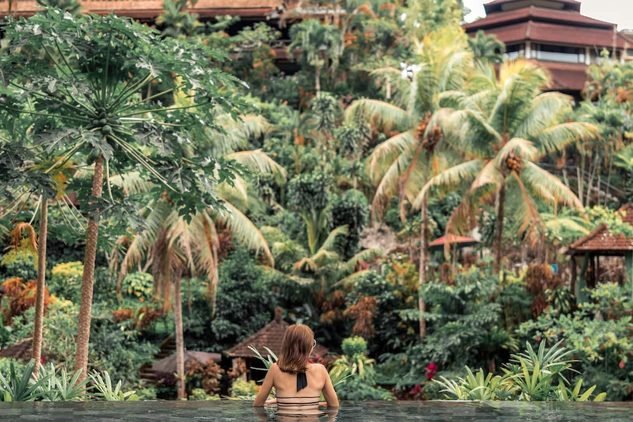 woman sitting in infinity pool overlooking forest area with palm trees and large cabins