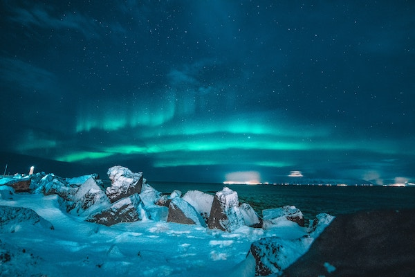 the Northern Lights glowing a blue/green color above snow covered rocks and reflecting off the cold waters