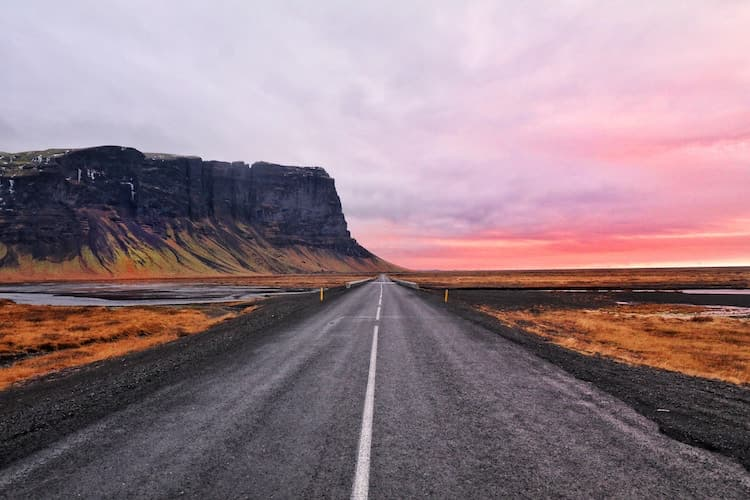 straight road leads towards steep cliff-face through orange grassland, with a orange/pink sunset in the distance
