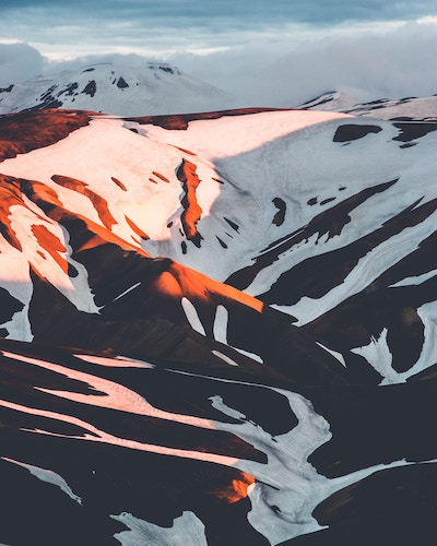 snow-covered icelandic mountains touching clouds and orange sunset