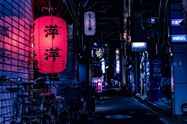 glowing red Japanese lantern stands out against dimly lit blue street with bicycles and shop signs