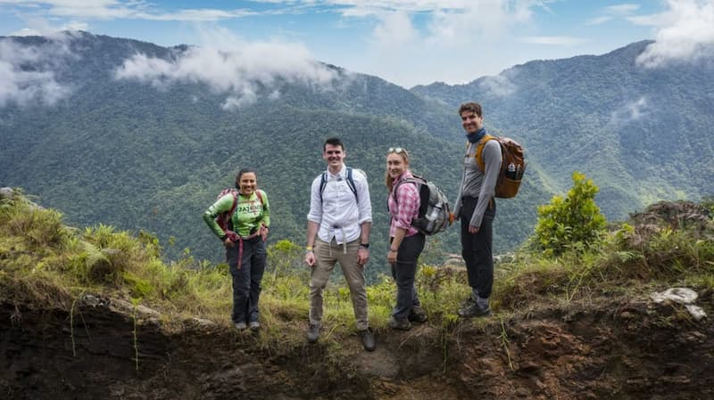 4 hikers with backpacks stood at the top of a mountain with another mountain in the distance