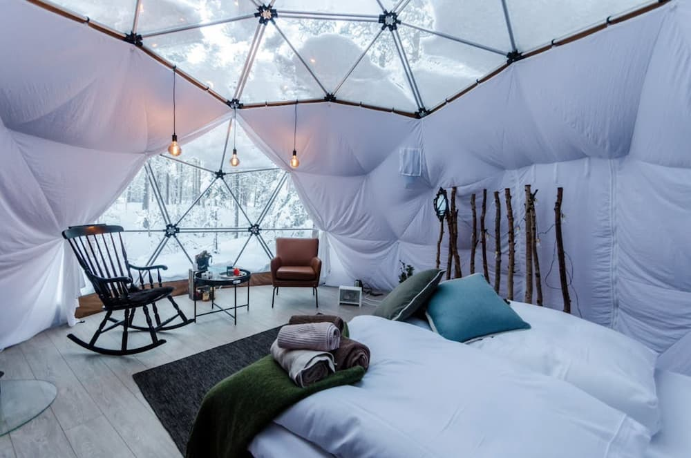 Inside of a canvas snow dome hotel room in Norway with snow outside the panes of glass