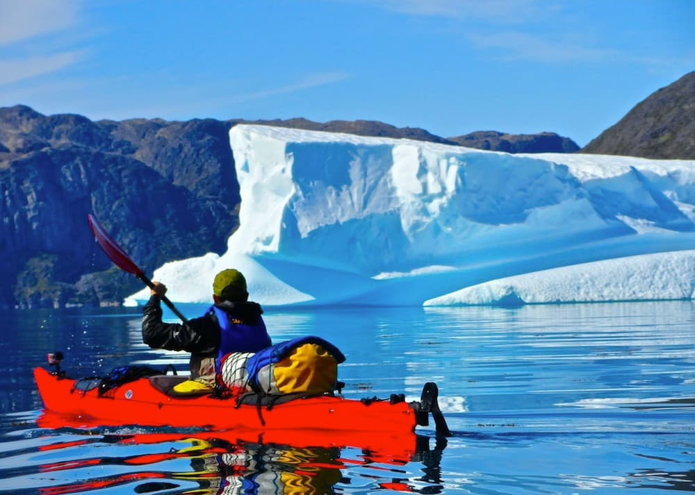 Solo-kayak in still water with ice cap in background