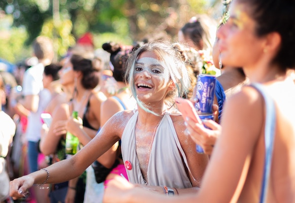 girl with silver face paint and dress smiling at a sunny festival