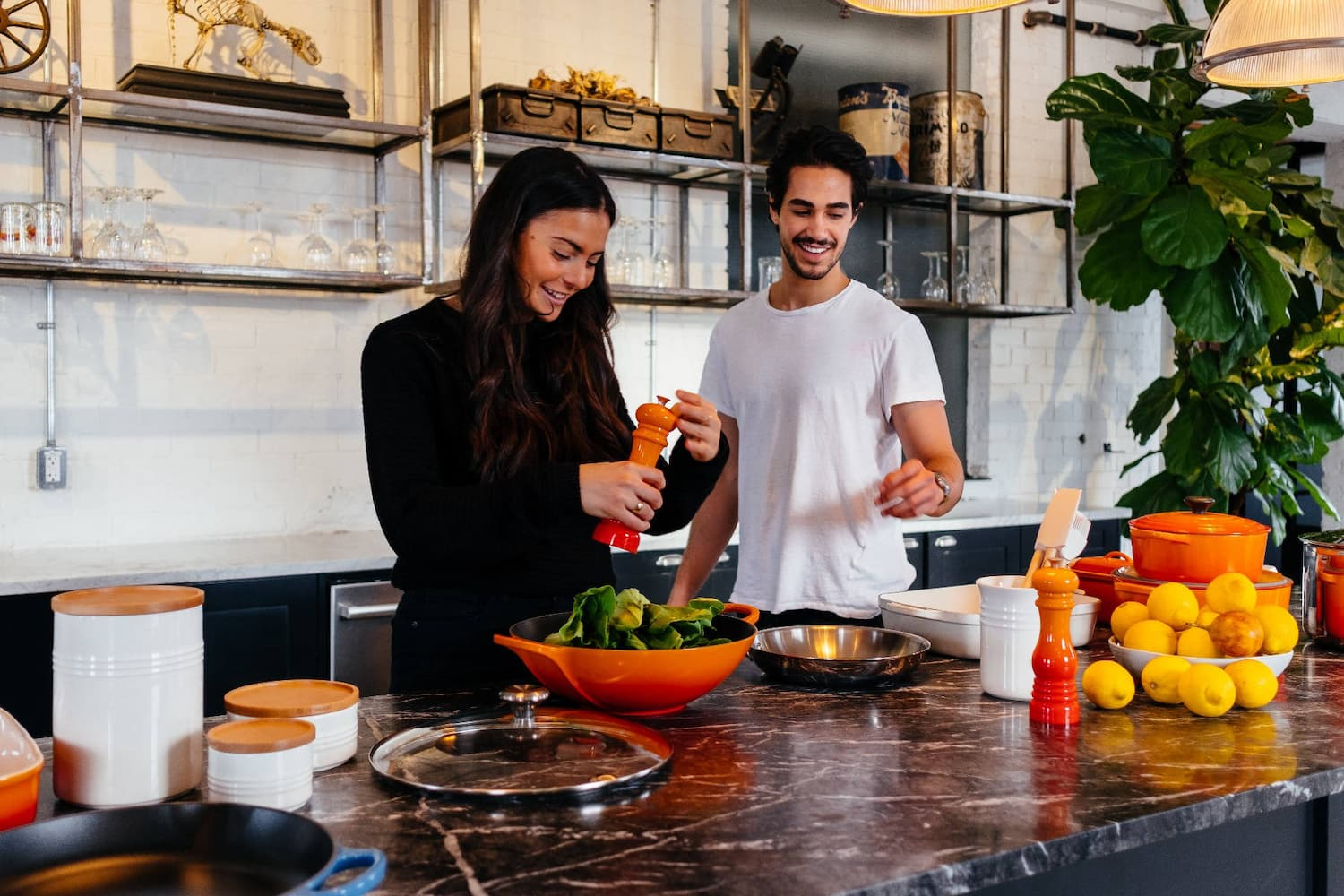 2 people smiling in a kitchen full of Le Creuset