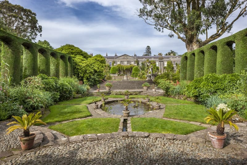 The gardens of a National Trust property, with a grand house in the background