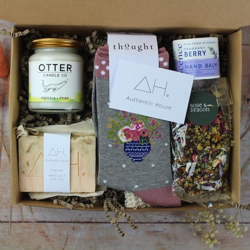 eco box filled with sustainable and ethical products, such as candles, soaps, and socks