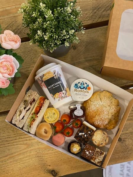 collection of afternoon tea items, including scones, sandwiches, clotted cream, and chocolates
