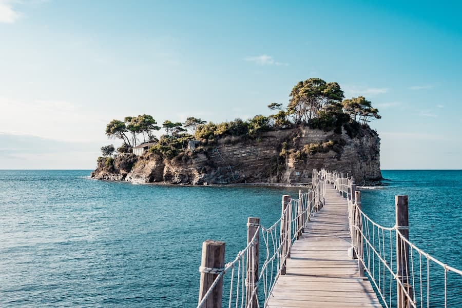 Wooden walkway with rope handrails crossing small part of the Mediterranean sea reaching tiny island with trees on