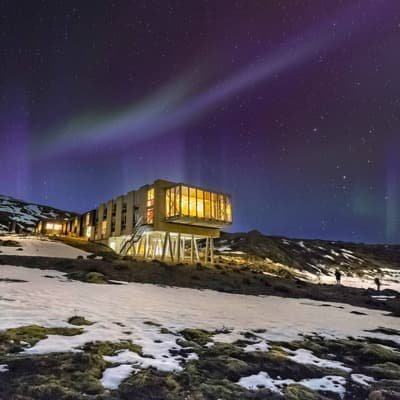 Modern hotel on snowy hillside with Northern Lights above